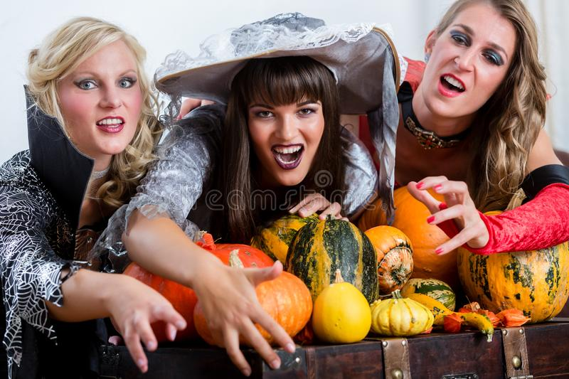 Four cheerful women celebrating Halloween together during costume party royalty free stock photos