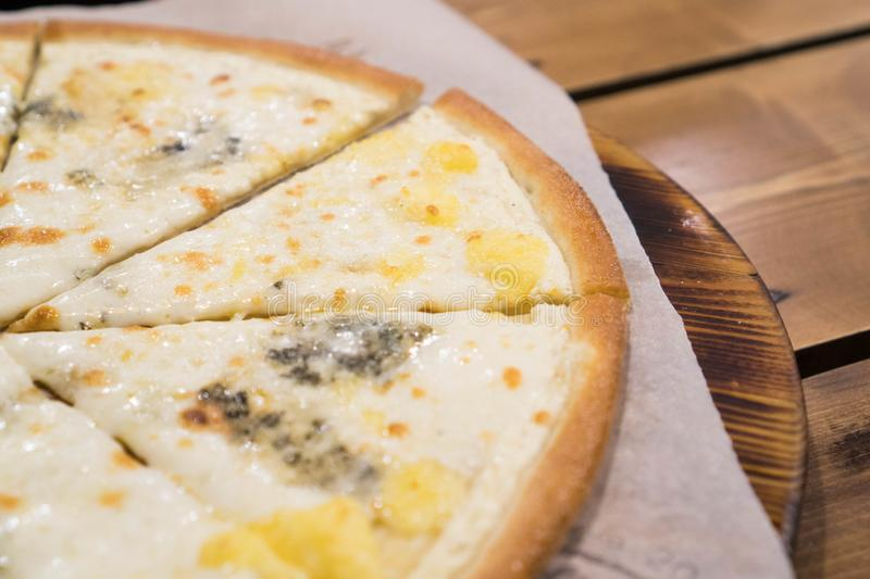 Four cheese pizza quattro fromaggi on a rustic dark colored wooden board background, close up.  stock images