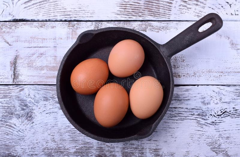 Four chicken eggs in a cast iron pan royalty free stock image