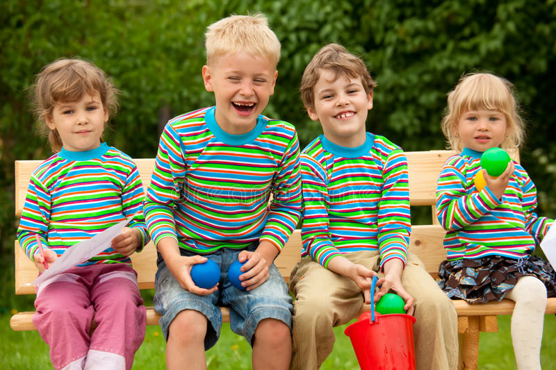 Download Four Children In Laugh Sitting On Bench Stock Image - Image: 12263237