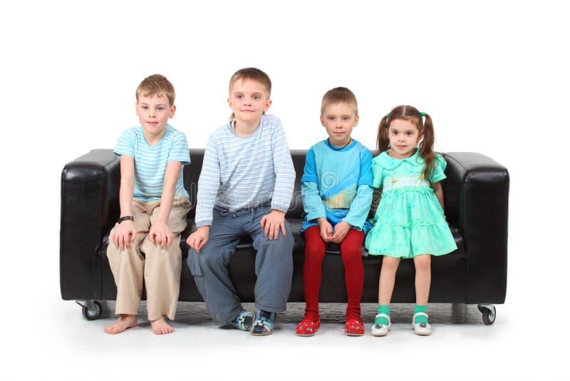 Four children sitting on black leather sofa royalty free stock photo