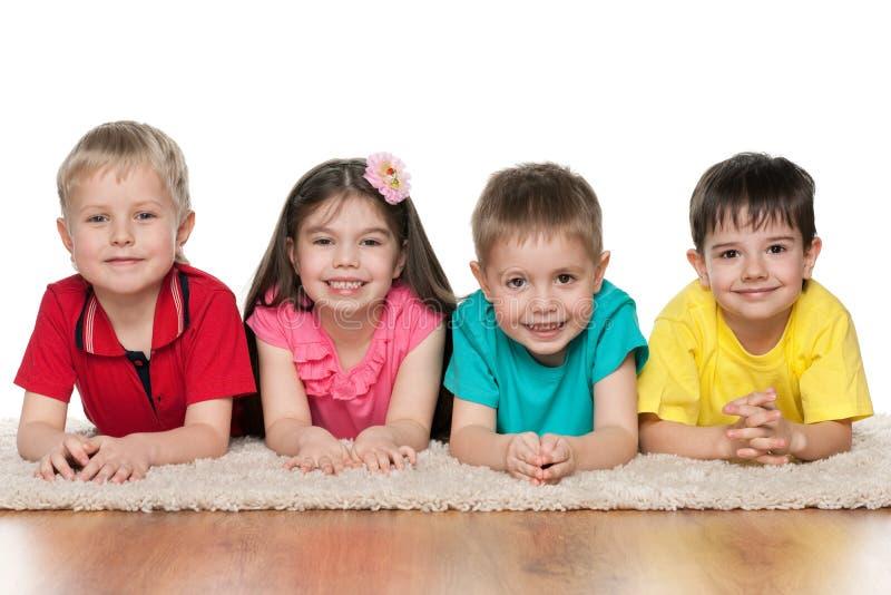 Four children on the white carpet royalty free stock photos