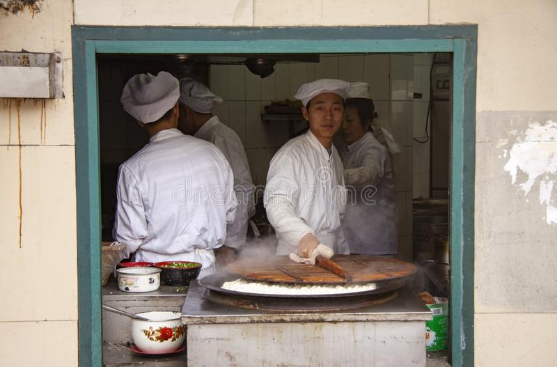 Four chinese chefs making traditional food in a kitchen - seen through an open window frame in a building at street level stock image