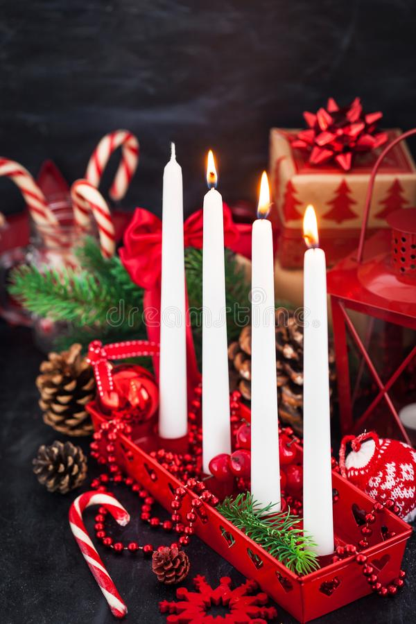 Four Christmas Advent candles and holiday decorations around on stock photo
