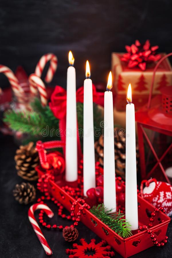 Four Christmas Advent candles and holiday decorations around on royalty free stock image
