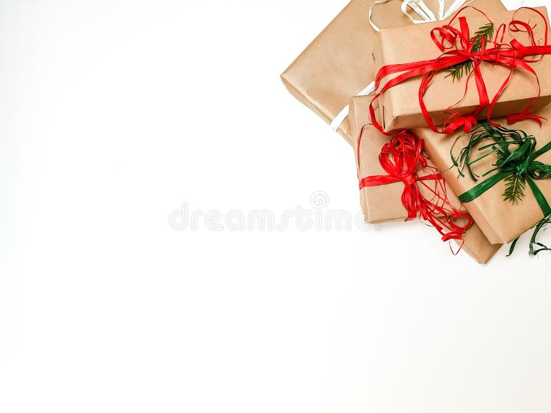 Four Christmas gift boxes crafted and red and green ribbons on a white background. Space to insert, text, top view stock photo