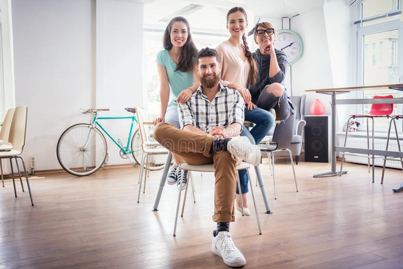 Four co-workers wearing casual clothes during work in a modern h royalty free stock images