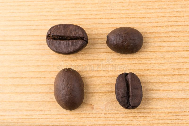 Four coffee beans in differen positions on wooden table stock photo
