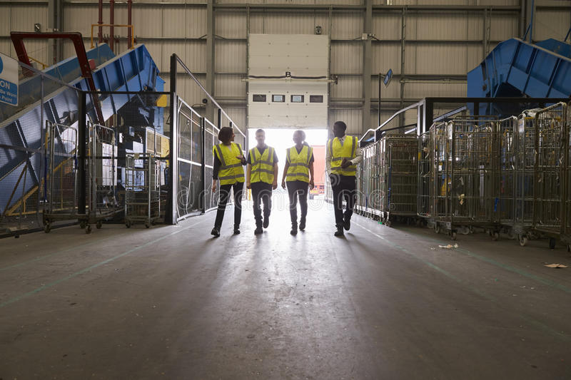 Four colleagues walking into a warehouse, wide view royalty free stock images