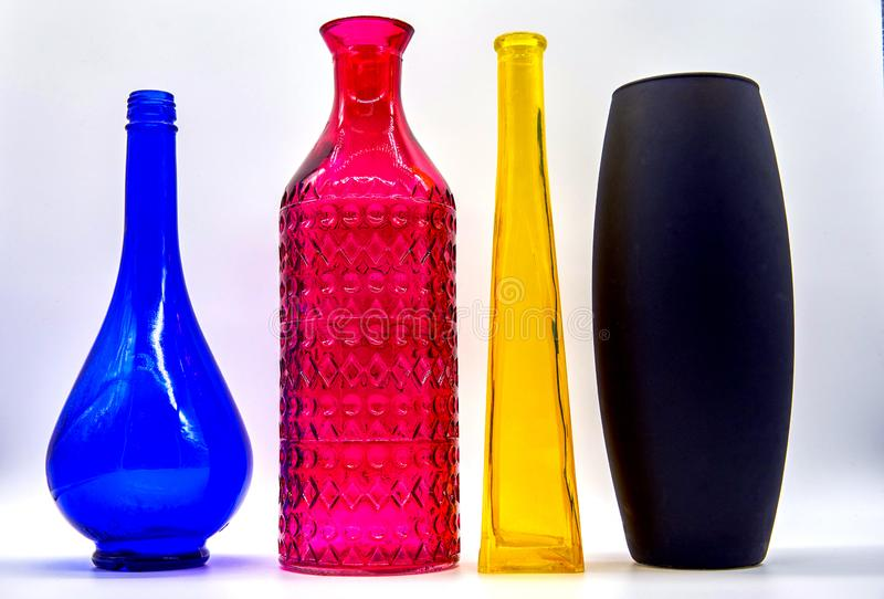 Four colored bottles are Radom, placed by color CMYK. Glass stock image