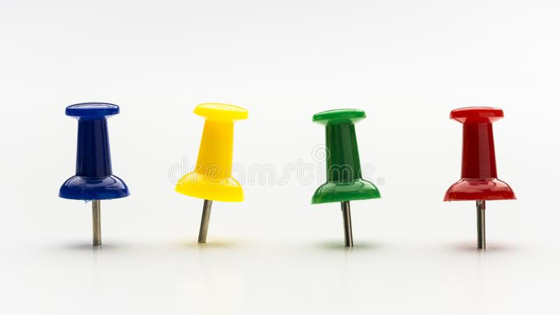 Four colored push pins in a row stock photos