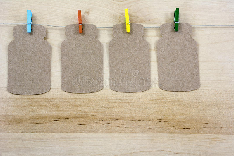Four colorful clothespins on the rope with notes. On the wooden background stock photography