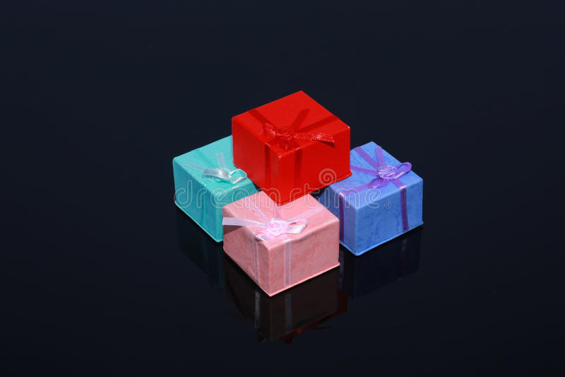 Four colorful gift boxes isolated on black. Background with reflection - Christmas valentines day, mothers day, fathers day, birthday gifts concept stock photos