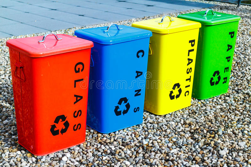 Four colorful recycling bins. Or containers labelled for glass, cans, plastic and paper standing in a row on gravel outdoors royalty free stock images