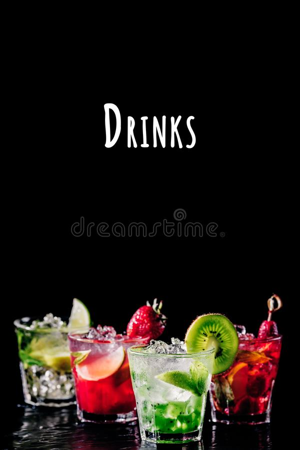 Four colorful tasty alcoholic cocktails in a row at the bar stand. Drinks wording royalty free stock photography