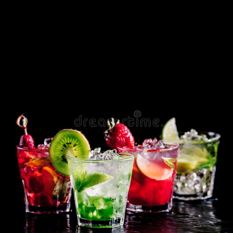 Four colorful tasty alcoholic cocktails in a row at the bar stand. stock photography