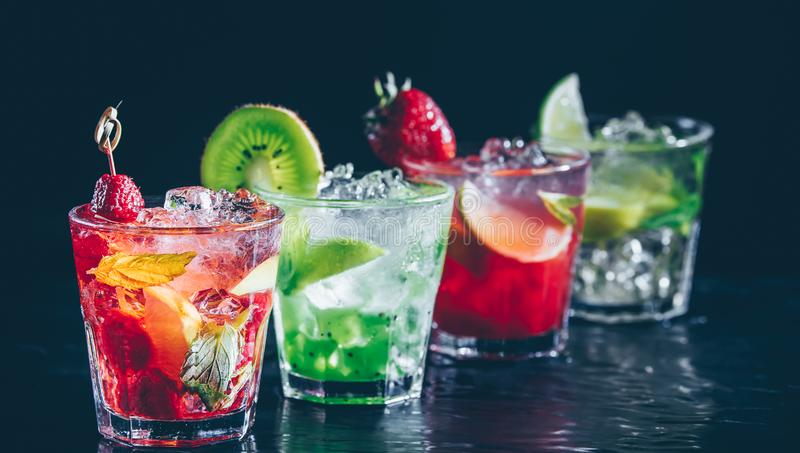 Four colorful tasty alcoholic cocktails in a row at the bar stand. stock image