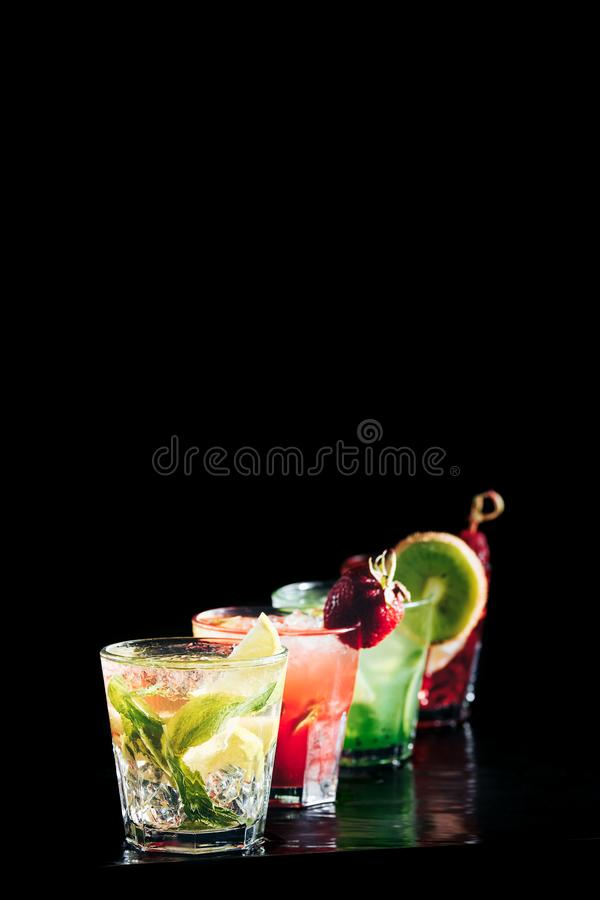 Four colorful tasty alcoholic cocktails in a row at the bar stand. royalty free stock images