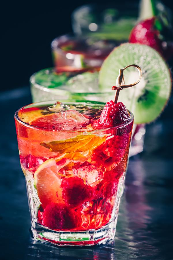 Four colorful tasty alcoholic cocktails in a row at the bar stand. royalty free stock photos