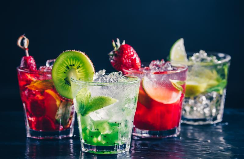 Four colorful tasty alcoholic cocktails in a row at the bar stand. royalty free stock photography