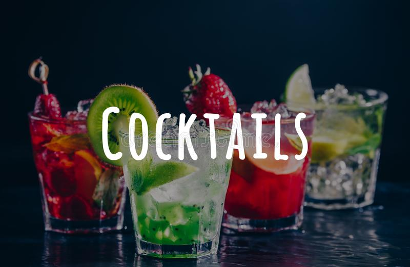 Four colorful tasty alcoholic cocktails in a row at the bar stand. Cocktails wording royalty free stock images