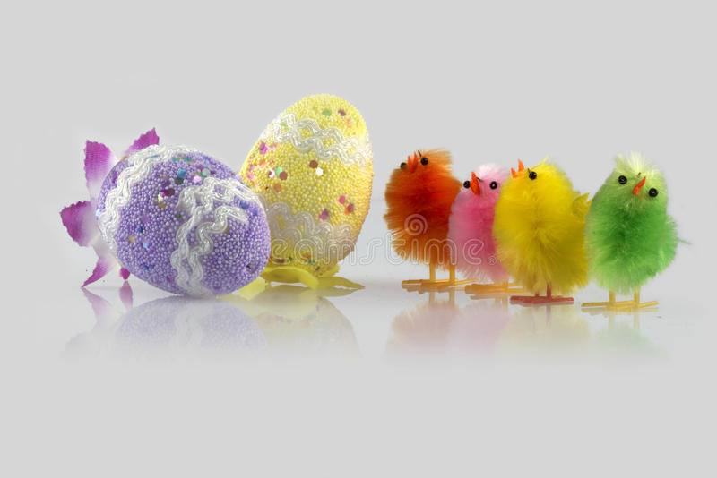 Easter decoration. Four colour Easter chick and two eggs decorated in a light grey background royalty free stock images
