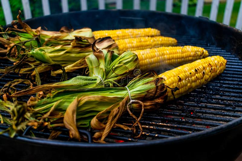 Corn on the cob cooking on a grill stock photos