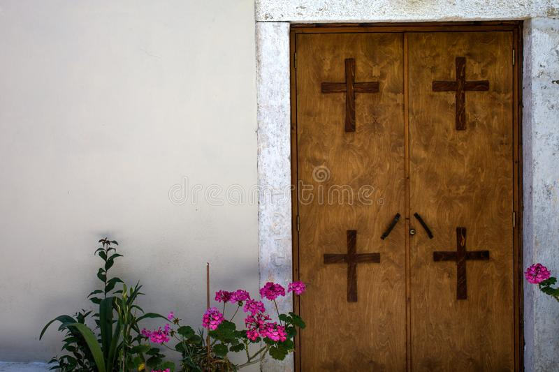 Four Crosses Mounted on Two Panel Closed Door. All Materials are made of Wood against White Cemented Wall. Plants with. Pink Flowers Placed at the Entrance stock photos