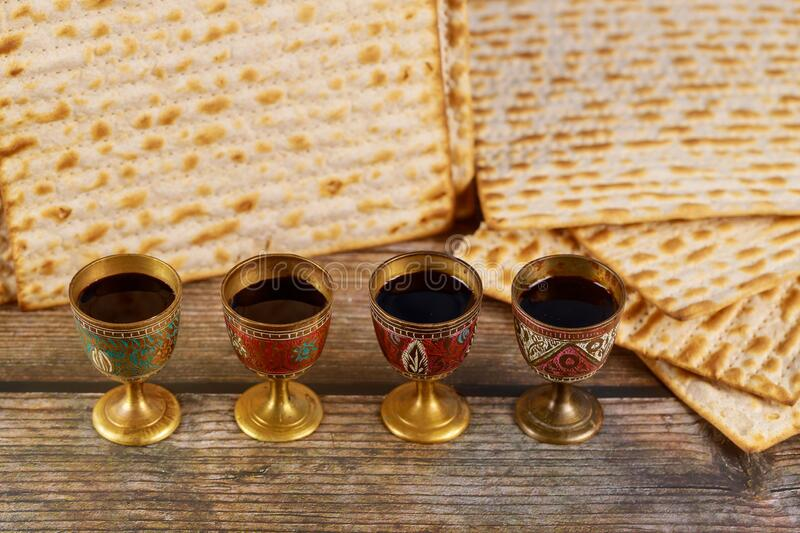 Four cups full of wine with matzah. Jewish holidays Passover royalty free stock photos