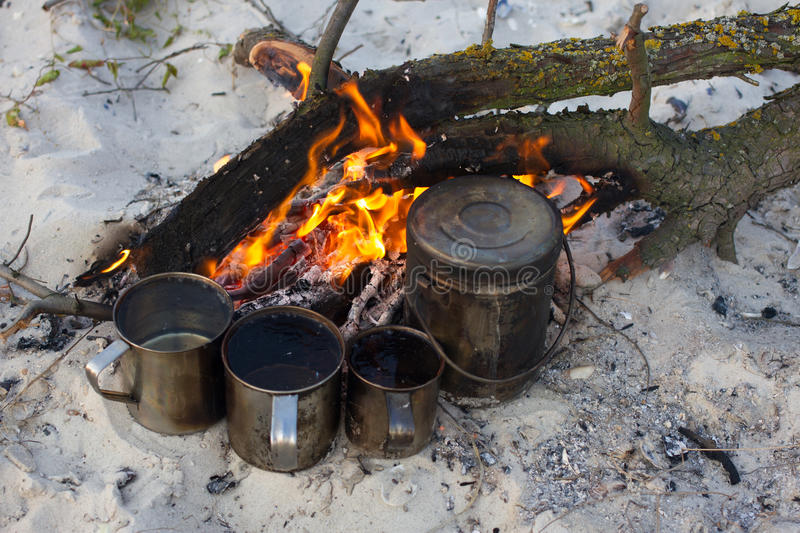 The four cups and kettle heats water on the fire. Camping beach, summer time, fireplace royalty free stock image
