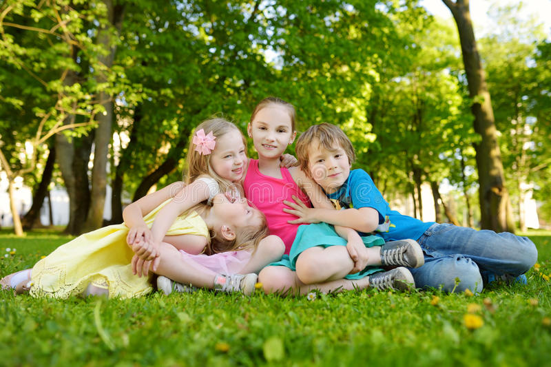 Four cute little children having fun together on the grass on a sunny summer day. Funny kids hanging together outdoors stock images