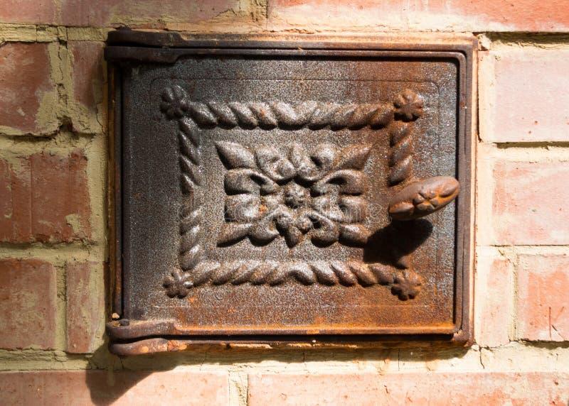 Four de brique rouge avec la fin de porte de fonte  photo stock