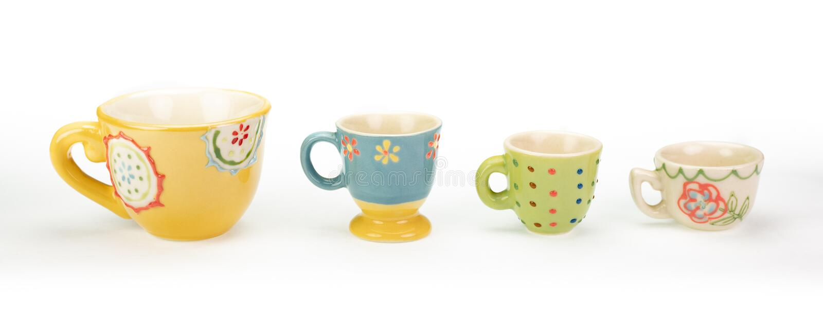 Four decorative ceramic teacups in a row. White background. stock image