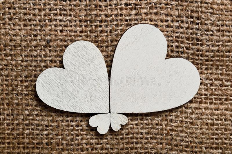 Four diferent size white wooden hearts assembled to flover shape on roug canvas textil background.  stock photos