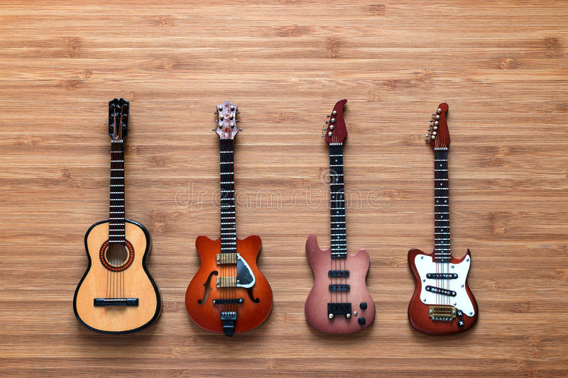 Four different electric and acoustic guitars on a wooden background. Toy guitars. Music concept. Four different electric, bass and acoustic guitars on a wooden royalty free stock photo