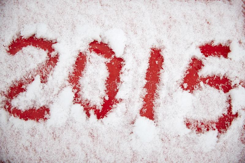 Four digits in the white snow. Pattern 2015 in red background stock photography