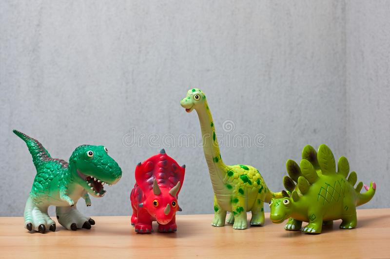 Four dinosaurs toys standing on a wooden floor. stock photos