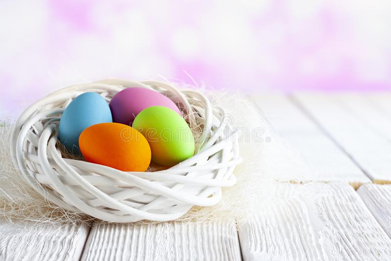 Four Easter eggs in white nest on table and pink abstract background stock images