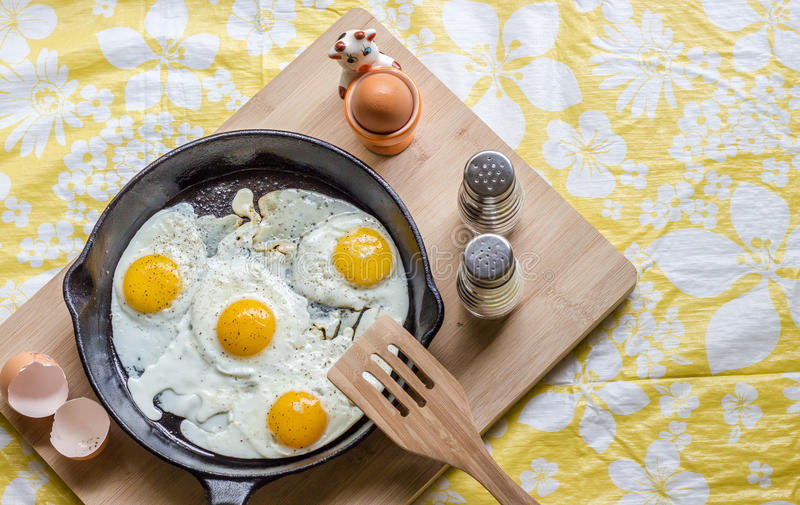 Four eggs cracked open in a cast iron pan on wood block royalty free stock photos