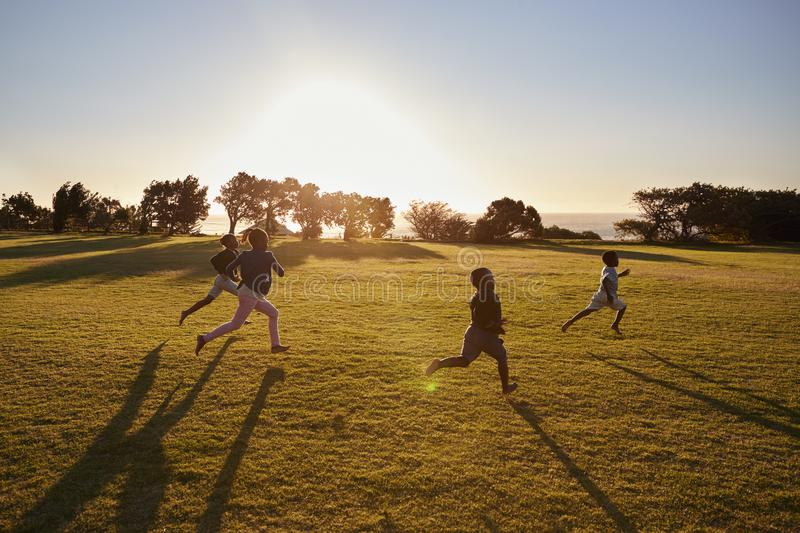Four elementary school children running in an open field stock photos