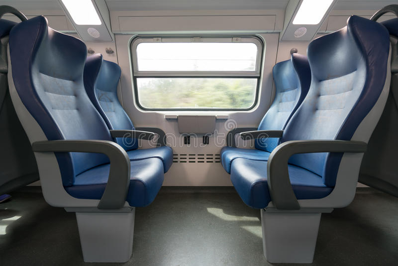 Four empty blue seats facing each other in modern European train. Railroad trip travel or transportation concept.  royalty free stock images