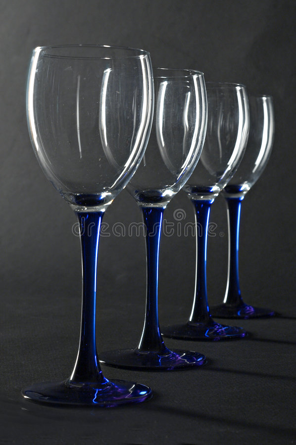 Four empty blue wine glasses royalty free stock images