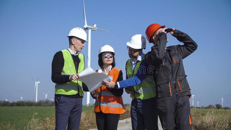Four engineers standing in open field. Four mixed ethnic people engineers and workers in multicolored jackets and hard hats standing in open field next to large royalty free stock photo