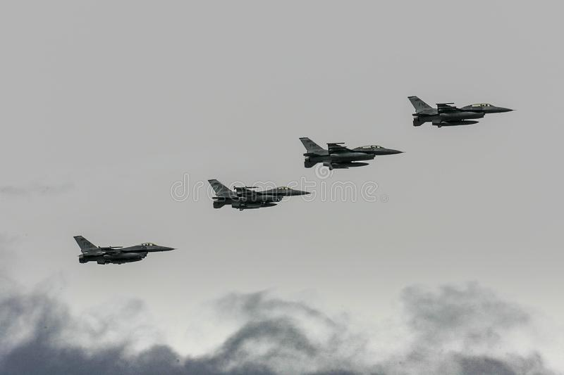 Four F-16 fighter jets above the clouds. A flight of four United States Air Force F-16 fighter jets viewed from the side as they fly in the cloudy sky over stock image