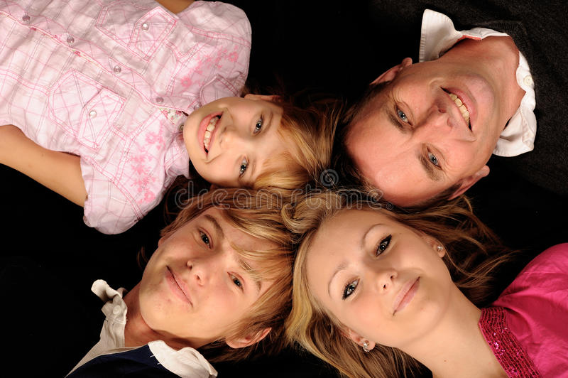 Four family members. Heads of four members of a family posed in a circle royalty free stock image