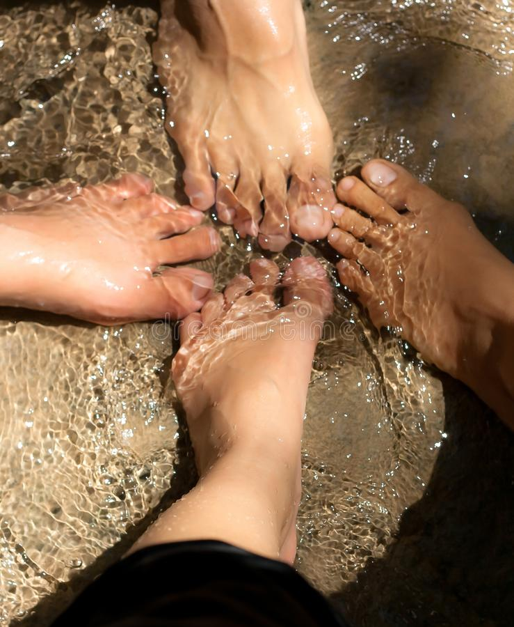 The Four feet from four person putting together in a shallow water in close up. royalty free stock photography