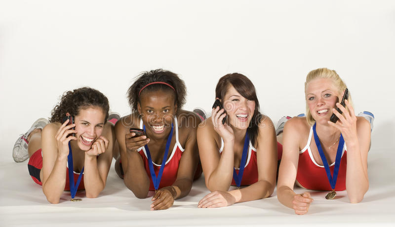 Four Female Athletes Lying Down, talking on Phones stock photography