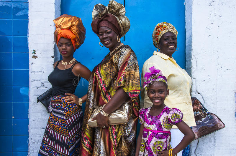 Four female celebrants of Emancipation Day pose against a wall on Picadilly Street, Port-of-Spain, Trinidad on Emancipation Day. Three women and one young girl stock photo