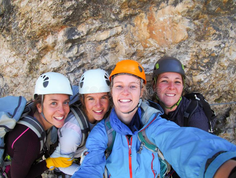 Four female climbers celebrate on the mountain summit by taking a group photo. View of four female climbers celebrating on the mountain summit by taking a group royalty free stock photography