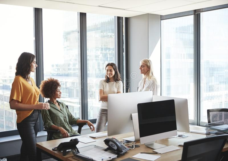Four female colleagues in discussion at a desk in a creative office, looking at each other royalty free stock photos